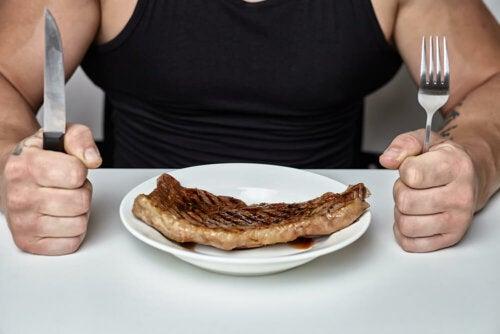 Uomo che mangia la bistecca