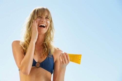 Donna che applica la protezione solare sul viso