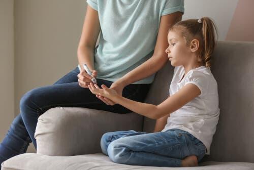 Madre misura la glicemia alla figlia