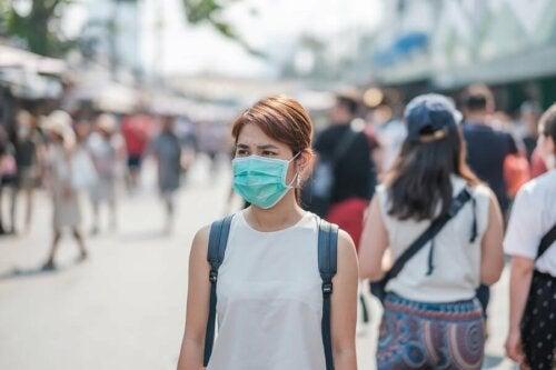 Donna con mascherina in strada affollata