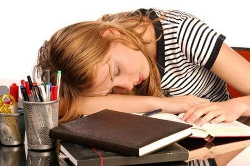 Ragazza addormentata sui libri per carenza di ferro