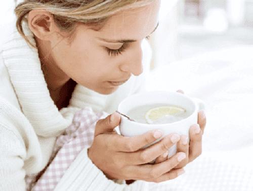 Donna malata con una tazza in mano.
