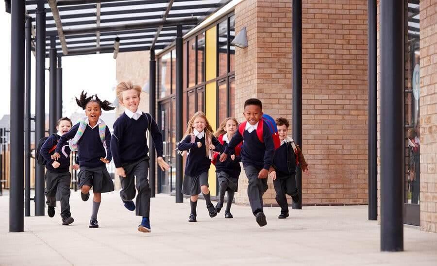 Bambini corrono all'uscita di scuola
