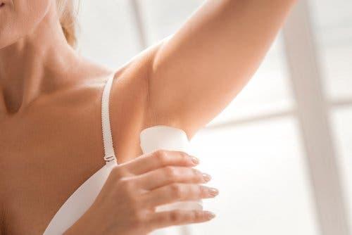 Donna applica il deodorante sotto le ascelle