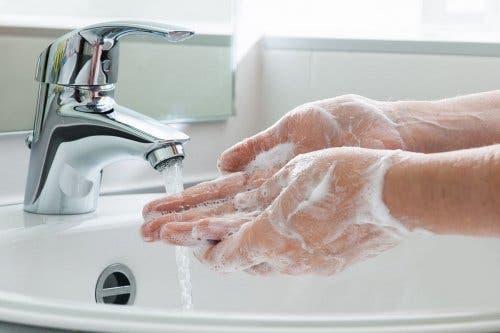 Mani insaponate sotto il getto dell'acqua