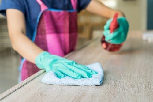 Donna pulisce una superficie di legno con panno e detergente