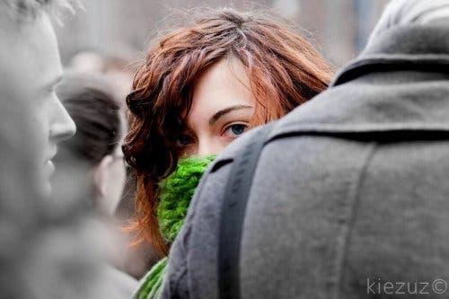 Filofobia, ragazza con sciarpa sul viso in mezzo alla folla