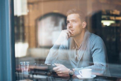 Uomo riflessivo seduto davanti a una finestra