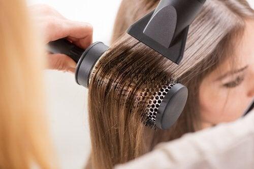 Asciugare i capelli con spazzola e phon.