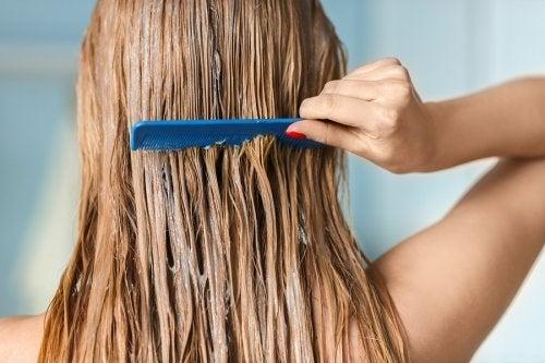 Ragazza che pettina i capelli con il balsamo.