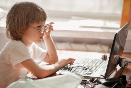 Bambino con occhiali davanti al pc