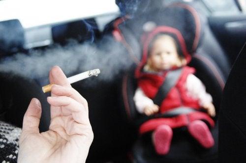 Bambino in auto subisce fumo passivo.