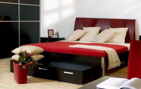 Camera da letto arredata con toni rossi.
