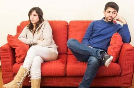 Coppia seduta distante sul divano.