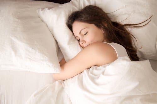 Donna addormentata che abbraccia il cuscino