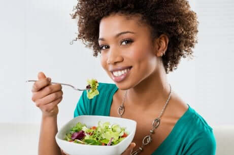 Donna che mangia una insalata.