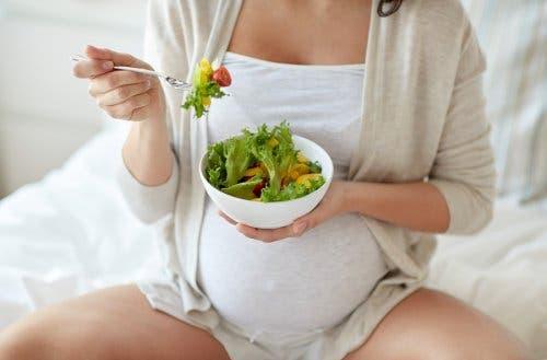 Donna incinta con ciotola di insalata