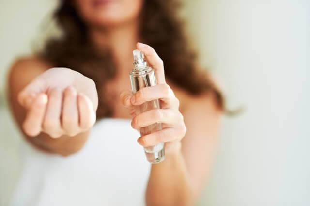 Donna che spruzza il profumo sul polso.