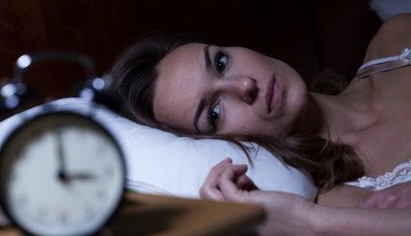 Donna che soffre di insonnia e guarda la sveglia.
