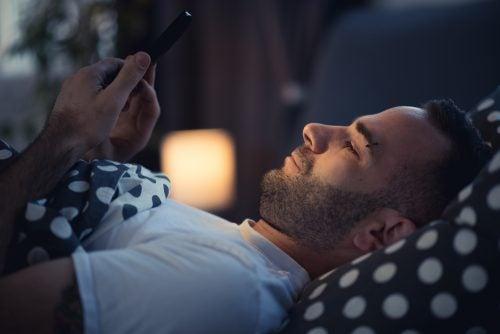 Ragazzo a letto con lo smartphone.