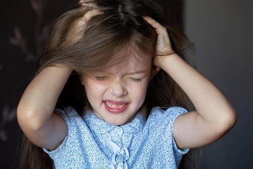 Bambina che si strappa i capelli.