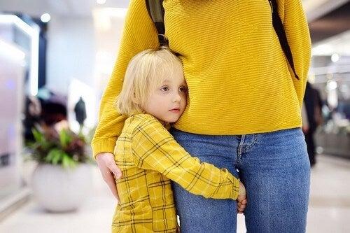 Bambina che abbraccia la mamma.