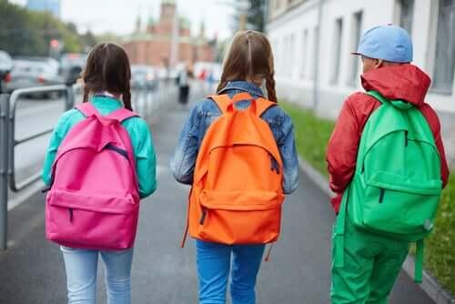 Tre ragazzi vanno a scuola indossando abiti e zaini colorati.