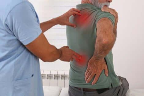 Uomo con  mal di schiena dal fisioterapista.