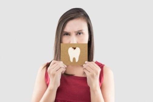Donna con cartoncino con dente cariato.
