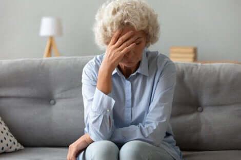 I rischi di un cancro alle ovaie aumentano nelle donne al di sopra dei 50 anni. Donna anziana preoccupata sul divano.