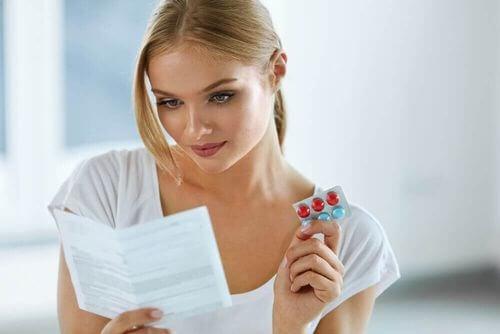 Donna che legge il foglietto illustrativo di un analgesico.