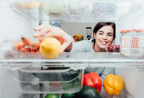 Ragazza che prende la verdura dal frigorifero.
