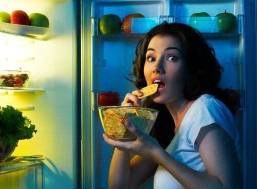 Ragazza davanti al frigo che mangia uno snack.
