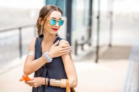 Ragazza applica crema solare sulle braccia.