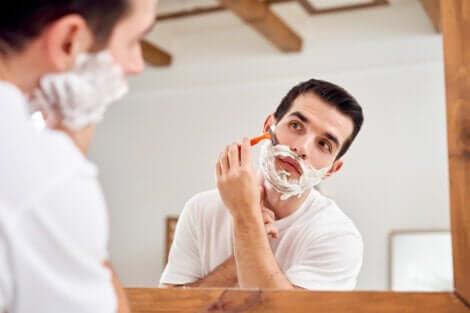 Uomo si fa la barba allo specchio.
