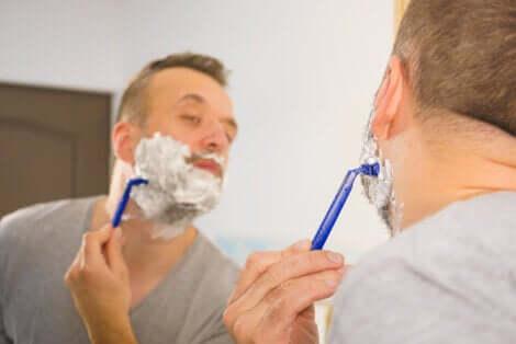 Uomo che si fa la barba davanti allo specchio.
