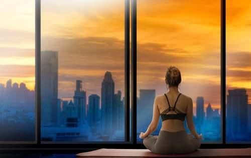 Donna che fa yoga davanti alla finestra.