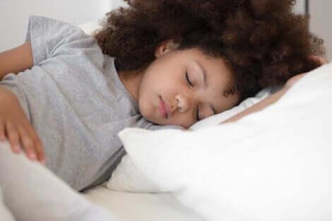 Bambina che dorme a letto.