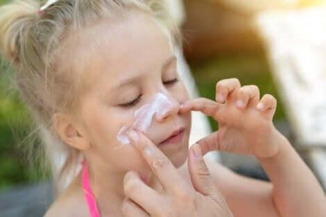 Mamma aiuta una bambina a spalmarsi la crema solare sul viso.