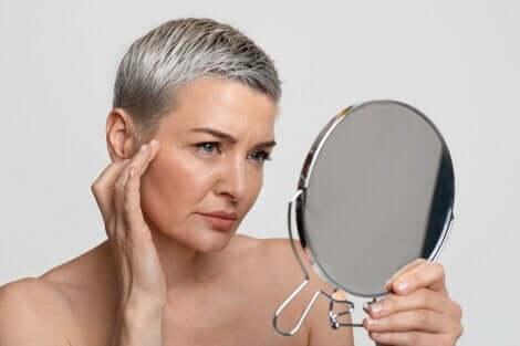 Donna che guarda le rughe del volto allo specchio.