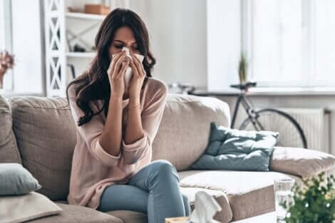 Donna con asma e rinite soffiandosi il naso.