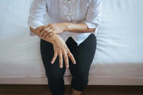 Paziente con il morbo di Parkinson seduto a letto con tremori.