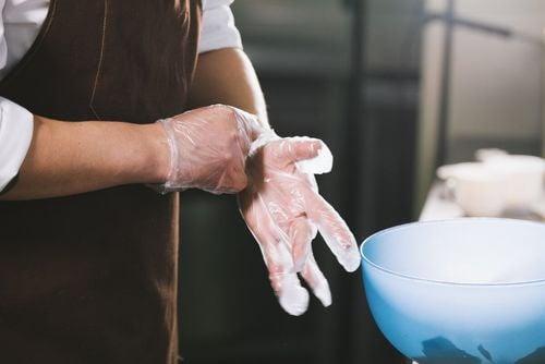 Uso di guanti per evitare la contaminazione crociata degli alimenti.