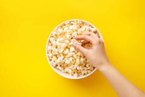 Mano prende un popcorn da una ciotola.