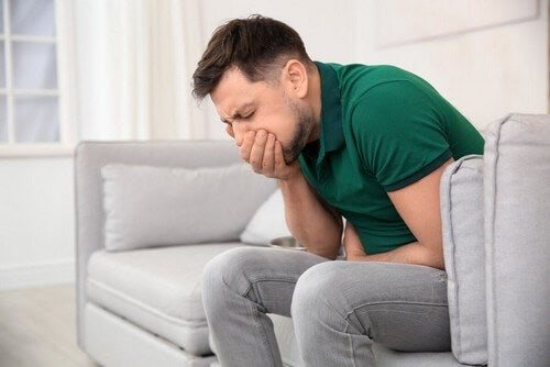 Ragazzo seduto sul divano con la nausea.