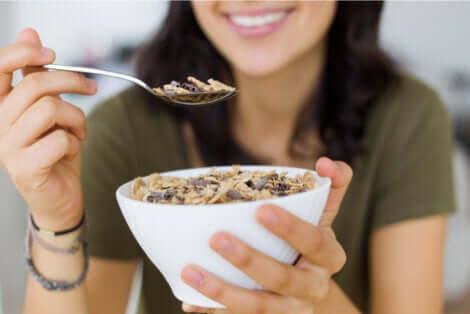 Ragazza che aggiunge i semi ai cereali per la colazione.