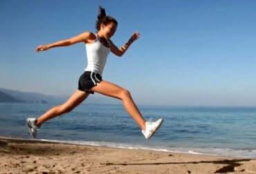 Ragazza che fa jogging lungo la spiaggia.