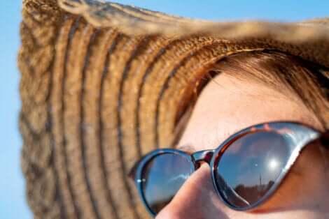 Viso femminile con occhiali da sole e cappello di paglia.
