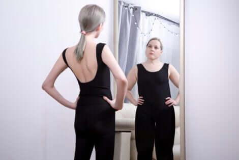 Adolescente magra allo specchio vede la propria immagine obesa.