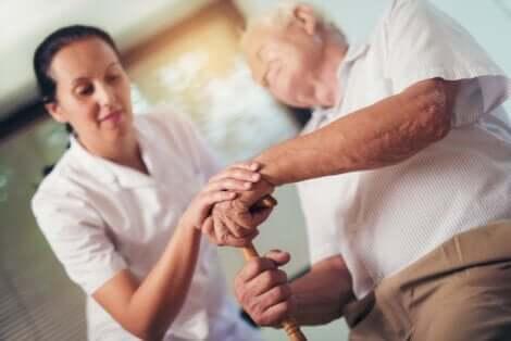 Infermiera che aiuta un signore anziano.